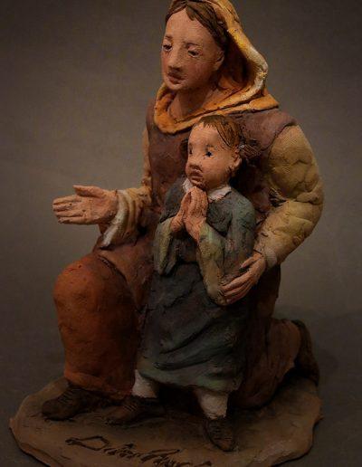 Madre inginocchiata accanto a bimba a mani giunte