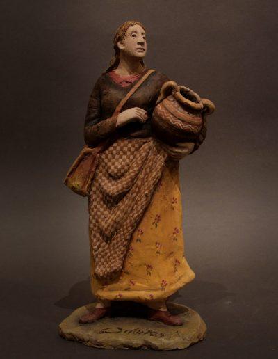 Donna in piedi con anfora e borsa a tracolla