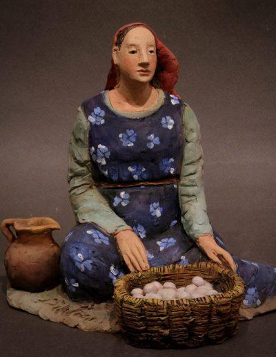 Donna con brocca e cesta di uova