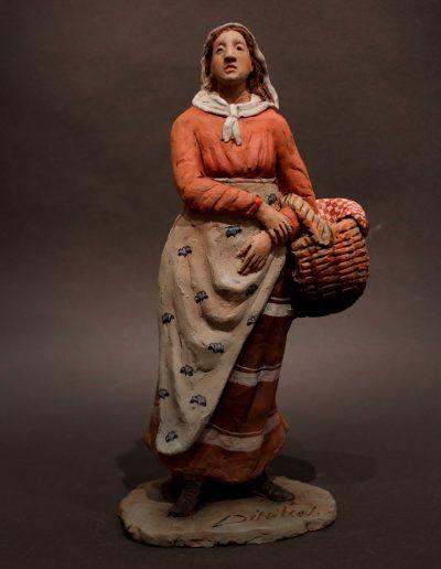 Donna in piedi con cesta al braccio
