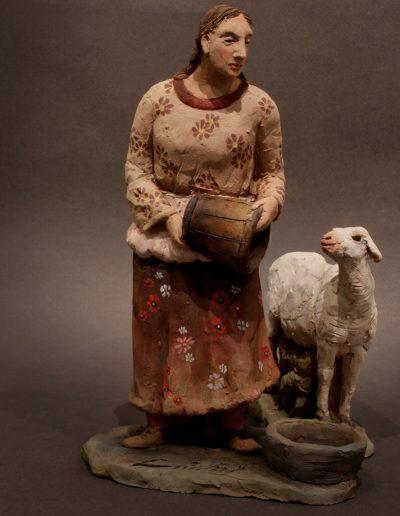 Donna con secchio e pecorella accanto