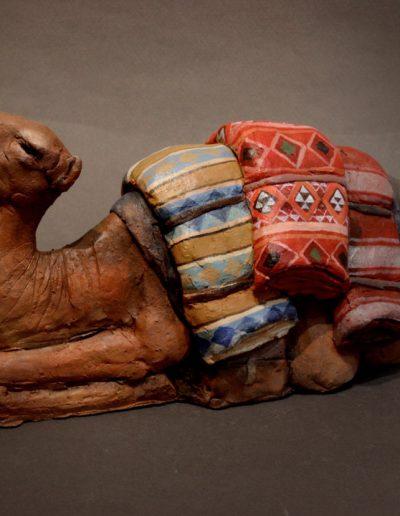 Dromedario accucciato con sella e drappi colorati