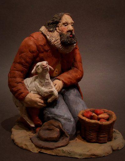 Pastore in ginocchio con pecorella e cesto di pere