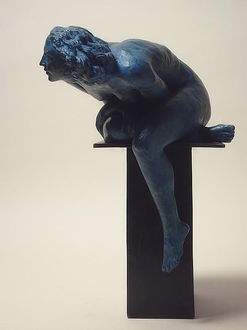 bronzo a sfumatura blu di nudo di donna seduta, che si sporge